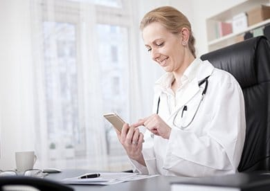 Smiling doctor looking at phone in office