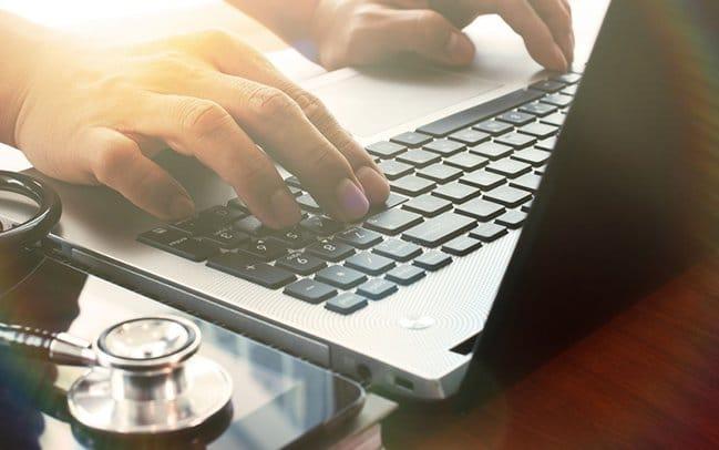 Doctor working on laptop | MyTeleMed | TeleMed Inc.