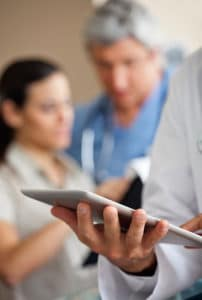 Doctor looking at iPad with nurse and patient in background| TeleMed Inc.